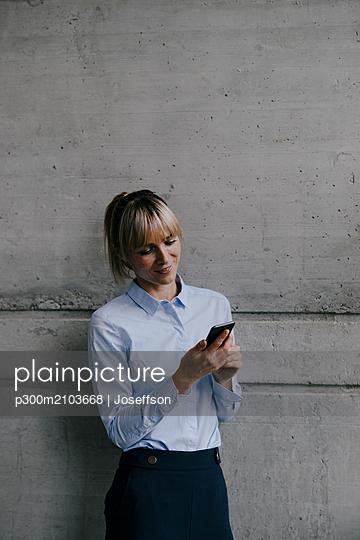 Blong businesswoman using smartphone, reading messages - p300m2103668 by Joseffson
