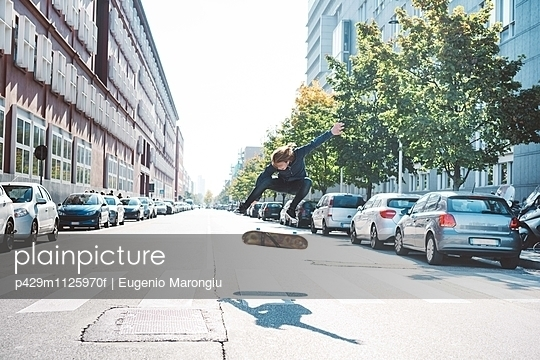 Young male urban skateboarder jumping mid air on pedestrian crossing