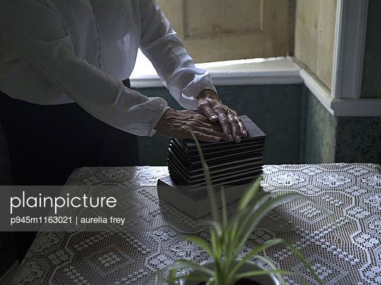 Frau legt ihre Hände auf Bücherstapel - p945m1163021 von aurelia frey