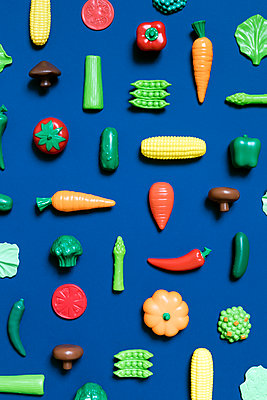 Directly above shot of various vegetable toys on blue background - p1094m1467614 by Patrick Strattner