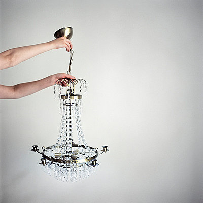 Low angle view of a person's hands holding a crystal chandelier - p3741720 by Leena Yla-Lyly