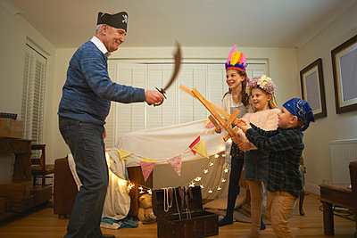 Senior man in pirate hat having sword fight with dressed up grandchildren - p429m1227274 by Peter Muller