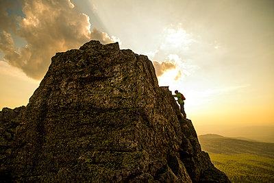 Caucasian hiker climbing on rock formation - p555m1411147 by Aleksander Rubtsov