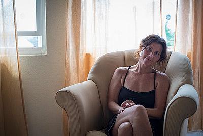 Caucasian woman sitting in armchair in living room - p555m1412372 by Alberto Guglielmi