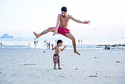 Mann springt über Sohn am Strand - p680m1511528 von Stella Mai