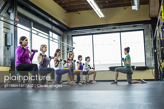 Instructor guiding women in lifting dumbbells at gym - p1166m1417402 by Cavan Images