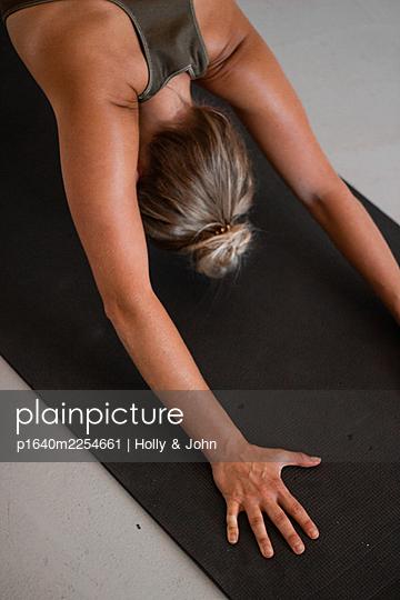 Junge Frau macht eine Yoga Übung - p1640m2254661 von Holly & John