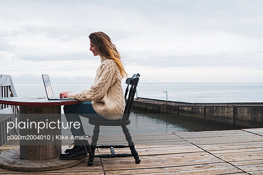 Iceland, woman using laptop at the sea - p300m2004010 von Kike Arnaiz