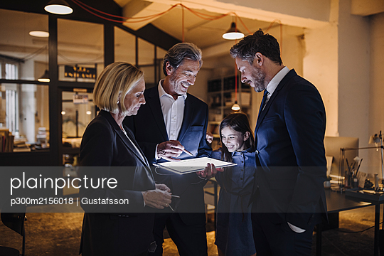Business people and girl looking at shining tablet in office - p300m2156018 by Gustafsson