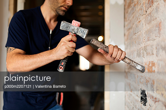 Construction worker using hammer and chisel at a brick wall - p300m2207121 by Valentina Barreto