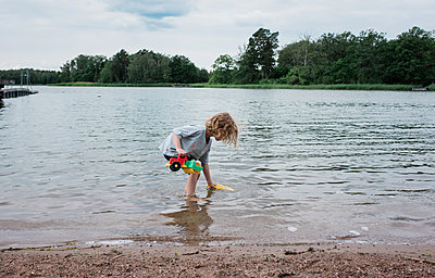 young girl playing with toys in the water at the beach in summer - p1166m2129941 by Cavan Images