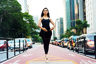 Brazil, Sao Paulo, Ballet dancer standing on tiptoes on bicycle lane - p300m1449716 by Valentina Barreto