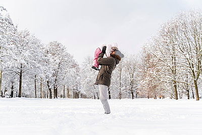 Happy affectionate father carrying daughter in winter landscape - p300m2083155 by Daniel Ingold