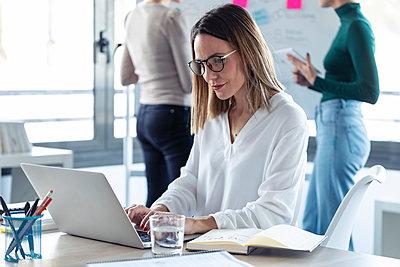 Female entrepreneur using laptop in an office - p300m2245968 by Josep Suria