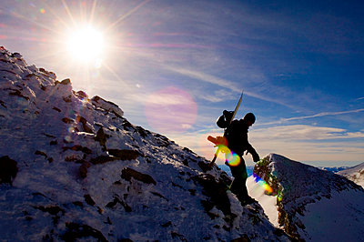 A Snowboarder hikes in the Tetons in Jackson Hole, Wyoming. - p343m964710 by Lucas Gilman