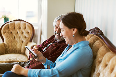 Happy senior man using smart phone with daughter in living room - p426m1468286 by Maskot