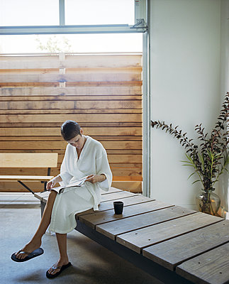 Woman reading magazine in spa - p555m1409537 by Shestock