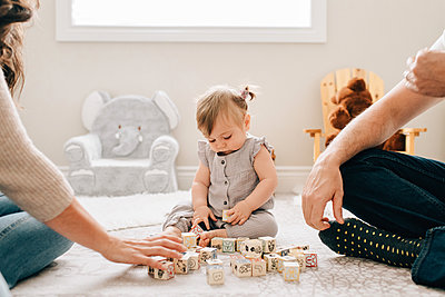 Mother and father on nursery floor with baby daughter playing with building blocks, cropped - p924m2097399 by Sara Monika