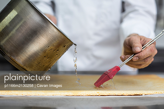 Chef soaking biscuit with syrup - p1166m2130258 by Cavan Images