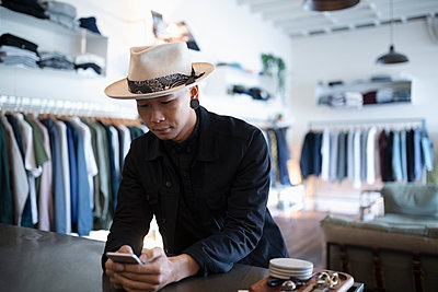 Male business owner using smart phone in menswear clothing shop - p1192m2062561 by Hero Images