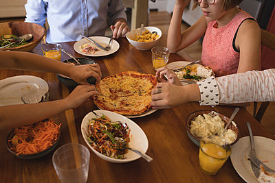 Family having pizza in kitchen - p1315m1579167 by Wavebreak