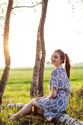 Smiling young woman sitting on a tree trunk and enjoying sunset - p300m2275385 by Jean Schwarz