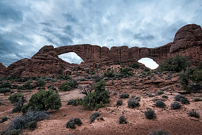 Low angle view of rock formations at Arches National Park against cloudscape - p1166m1532250 by Cavan Social
