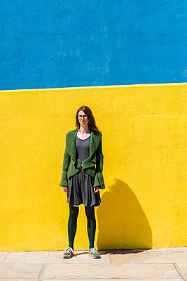 Portrait of confident businesswoman standing on sidewalk against colorful wall during sunny day - p1166m2060574 by Cavan Social