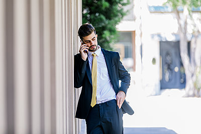 Atractive man with suit talking on phone outdoor in bright day - p1166m2095195 by Cavan Images