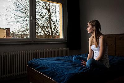 Frau auf Bett sitzend - p1611m2182306 von Bernd Lucka