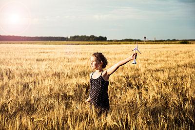 Girl standing in grain field holding miniature wind turbine - p300m1499490 by Robijn Page