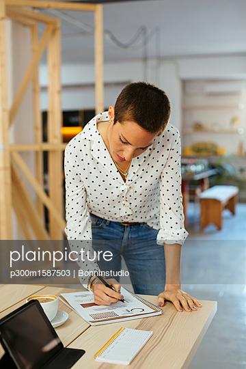 Woman working on draft at desk in office - p300m1587503 von Bonninstudio