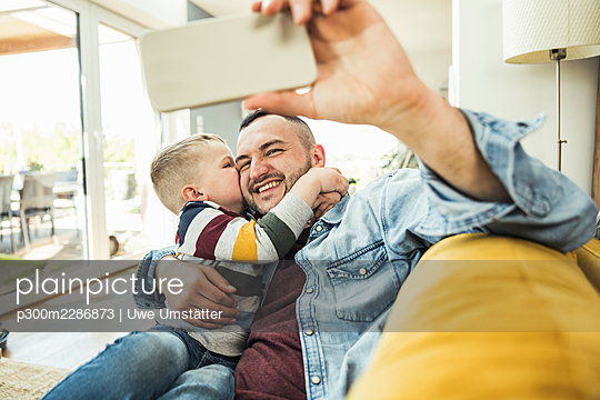 Son kissing on cheek while father taking selfie selfie through mobile phone on living room - p300m2286873 by Uwe Umstätter