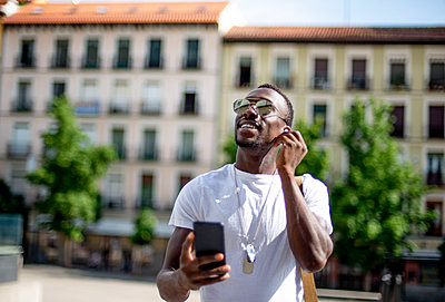 Smiling young man using smartphone and ear phones, looking up - p300m2139722 by Jesús Martinez