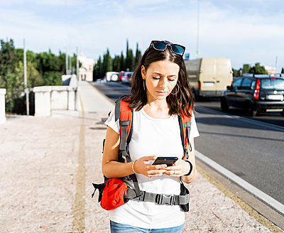 Young female backpacker with red backpack using smartphone in the city, Verona, Italy - p300m2143777 by Giorgio Fochesato