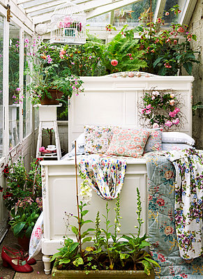 White single bed with floral quilts in conservatory of Isle of Wight home;  UK - p349m920072 by Rachel Whiting