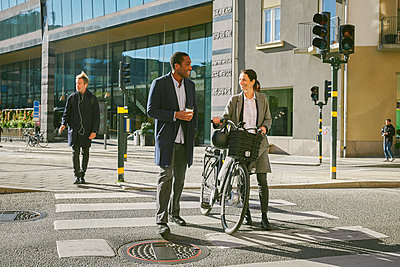 Full length of smiling man and woman talking while walking with electric bicycle on crosswalk against building in city - p426m2075130 by Maskot