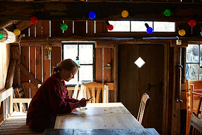 Side view of young woman using smart phone while sitting at table in log cabin - p426m2118330 by Maskot