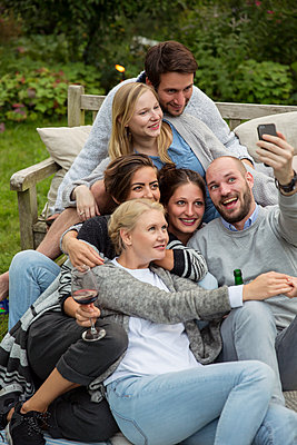 Friends taking a selfie on garden party - p788m1165288 by Lisa Krechting