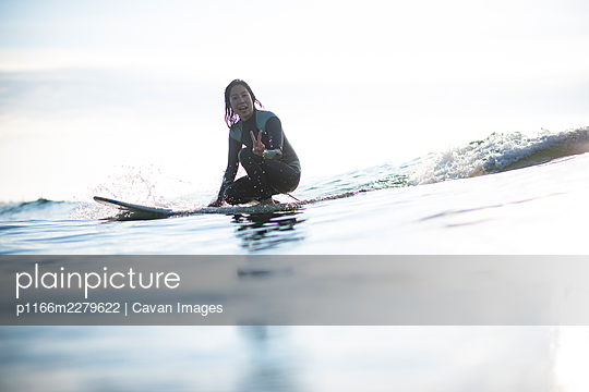 Asian Woman having fun on waves during sunrise summer surf session - p1166m2279622 by Cavan Images