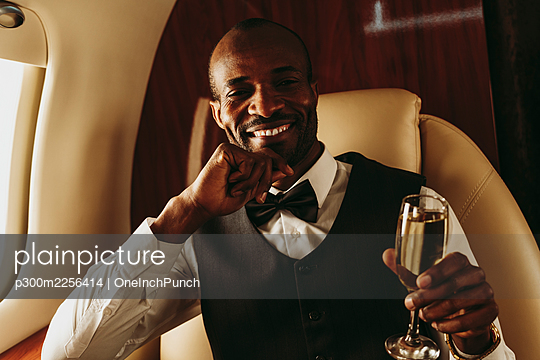 Male entrepreneur with hand on chin holding champagne in airplane - p300m2256414 by OneInchPunch
