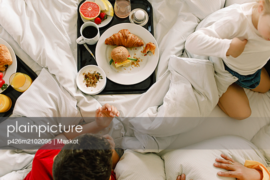 Directly above shot of family having breakfast on bed in hotel - p426m2102095 by Maskot