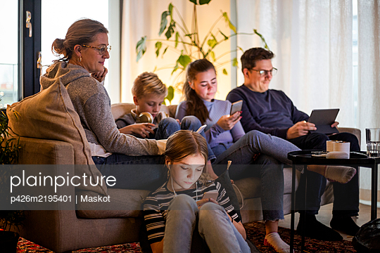 Parents sitting with children while using wireless technologies in living room at modern home - p426m2195401 by Maskot