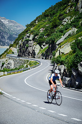 Bicyclist riding on serpentine mountain road - p1053m2005715 by Joern Rynio