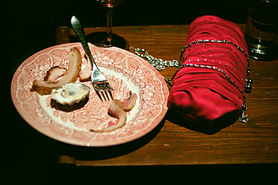 Empty buffet plate on table by clutch bag - p1072m830529 by Neville Mountford-Hoare