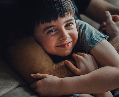 Midsection of father embracing happy son while lying on sofa at home - p1166m2001038 by Cavan Images