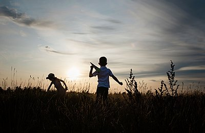 silhouette of siblings playing with paper planes outside at sunset - p1166m2137851 by Cavan Images