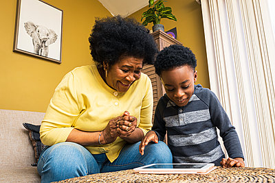 Cheerful boy and grandmother playing video game on digital tablet at h - p1166m2279399 by Cavan Images