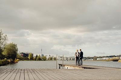Two businessmen standing on jetty at a lake talking - p300m1535311 by Kniel Synnatzschke