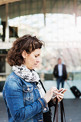 Side view of businesswoman using mobile phone outside railroad station - p426m1085317f by Kentaroo Tryman